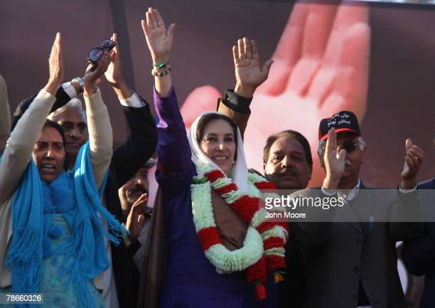 Former Prime Minister Benazir Bhutto waves to supporters at a campaign rally minutes before she was assassinated in a bomb attack December 27 2007 in...