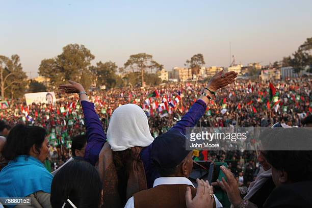 Former Prime Minister Benazir Bhutto waves to thousands of supporters at a campaign rally minutes before being assassinated in a bomb attack December...