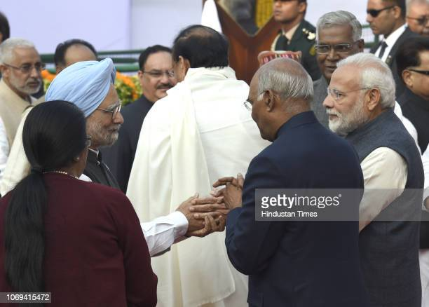 Former Prime Minister Manmohan Singh greets Prime Minister Narendra Modi as President Ram Nath Kovind looks during an event to pay tribute to BR...