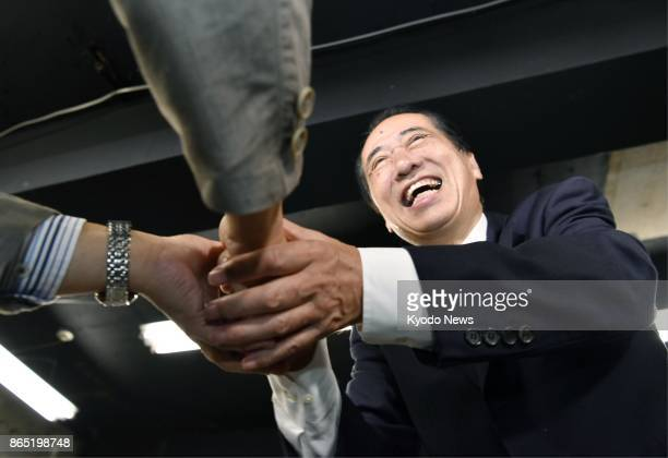 Former Prime Minister Naoto Kan celebrates on Oct 23 after prevailing in a close race in a singleseat constituency in Tokyo in the general election...