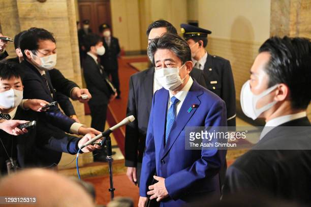 Former Prime Minister Shinzo Abe is surrounded by media reporters after attending the Lower House Rules and Administration Committee for damaging the...