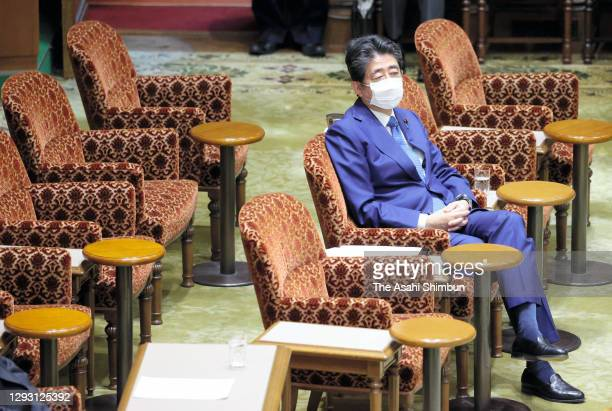 Former Prime Minister Shinzo Abe listens to a question during Lower House Rules and Administration Committee for damaging the trust of the Diet by...