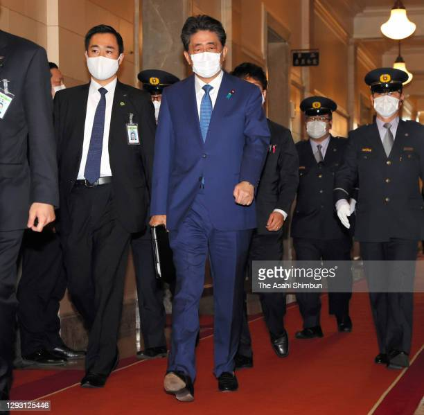 Former Prime Minister Shinzo Abe walks to attend the Lower House Rules and Administration Committee for damaging the trust of the Diet by making...