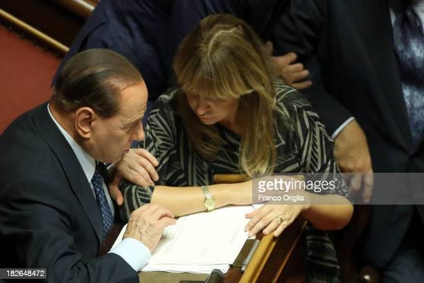 Former Prime Minister Silvio Berlusconi chats with Senator Alessandra Mussolini during the confidence vote for Enrico Letta's government at the...
