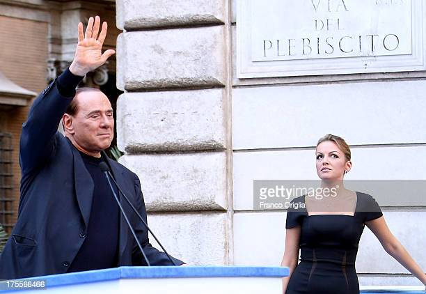 Former Prime Minister Silvio Berlusconi flanked by his new girlfriend Francesca Pascale waves to his supporters during a ProBerlusconi rally outside...