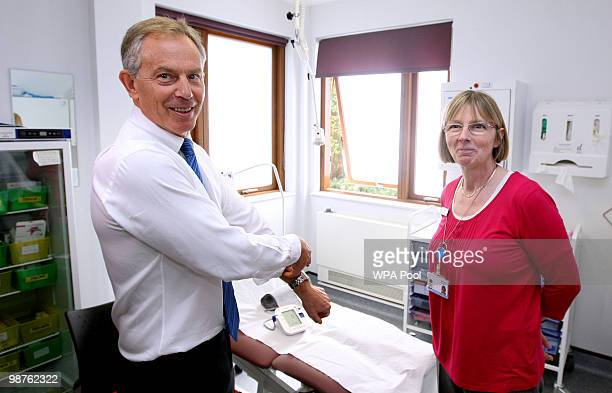 Former Prime Minister Tony Blair rolls up his sleeve to have his blood pressure taken by Nurse Paula Martin during a visit to Alexandra Avenue Health...