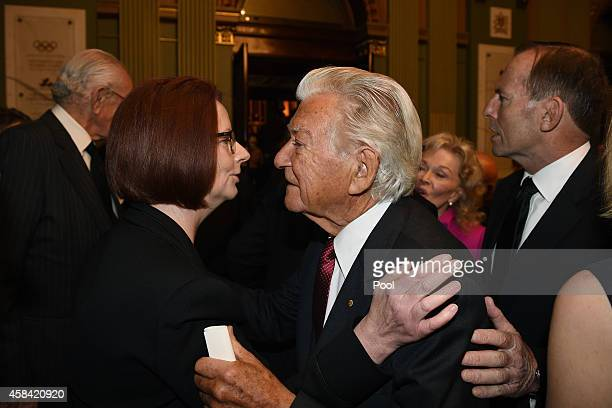 Former Prime Ministers Julia Gillard and Bob Hawke greet each other following the state memorial service for former Australian Prime Minister Gough...