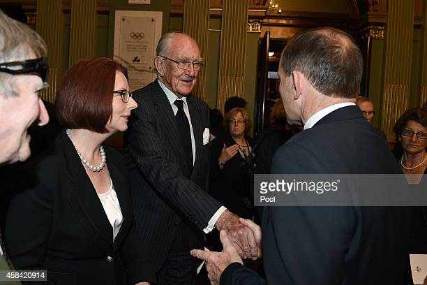 Former Prime Ministers Julia Gillard and Malcolm Fraser are greeted by Prime Minister Tony Abbott following the state memorial service for former...