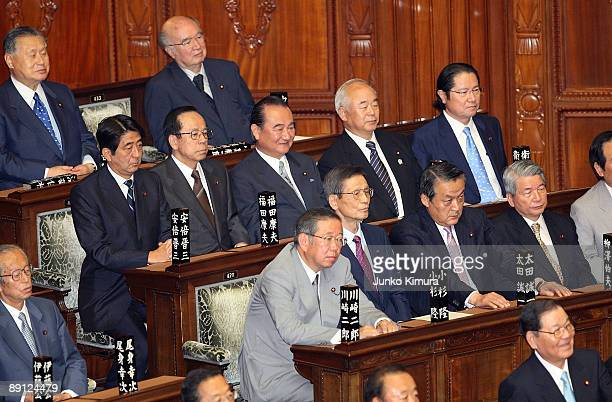 Former Prime Ministers Shinzo Abe and Yasuo Fukuda and other members of the House of Representatives attend the plenary session at the lower house on...