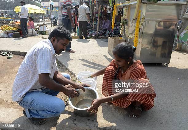 Former prisoner Marineni Raju and his wife Marineni Priyanka clean utensils at their newly opened tea stall in Hyderabad on February 11 2014 Raju who...