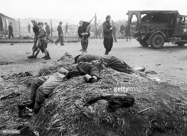 Former prisoners of Bergen Belsen concentration camp walking past some of the dead bodies strewn around the camp after it was liberated by the forces...
