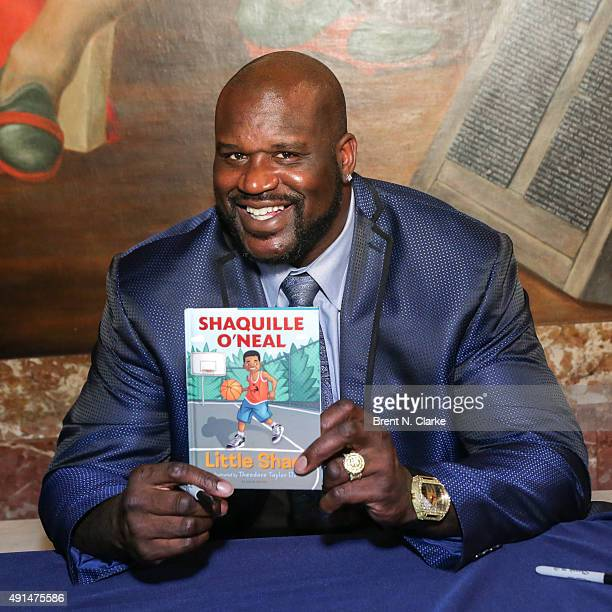 Former professional basketball player/author Shaquille O'Neal displays a copy of his newest book during LIVE from the NYPL Shaquille O'Neal held at...