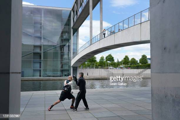 Former professional boxers Fabio Frittoli and Fabio Brusco spar on the banks of the Spree River among office buildings of the Bundestag during the...