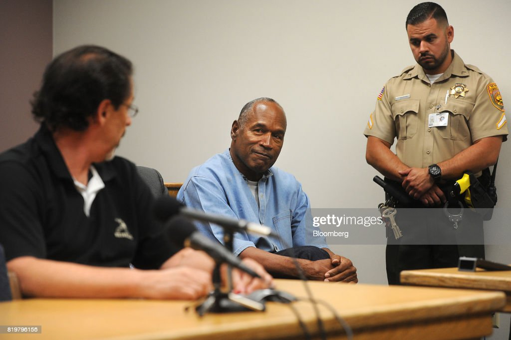 Former professional football player O.J. Simpson, center, smiles as Bruce Fromong testifies during a parole hearing at Lovelock Correctional Center in Lovelock, Nevada, U.S., on Thursday, July 20, 2017. Simpson has been granted parole nine years into a 33-year sentence and could be released as soon as Oct. 1. Photographer: Jason Bean/Pool via Bloomberg