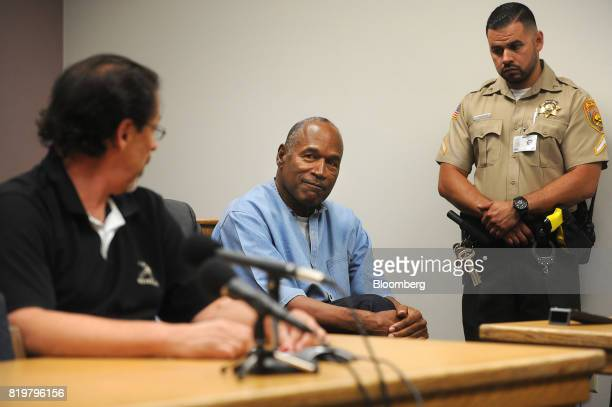 Former professional football player O.J. Simpson, center, smiles as Bruce Fromong testifies during a parole hearing at Lovelock Correctional Center...