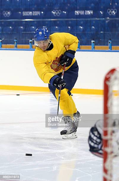 Former professional hockey player Alexei Yashin shoots the puck during a Russian women's ice hockey team practice session prior to the Sochi 2014...