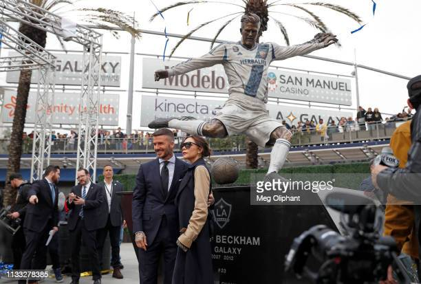 Former professional soccer midfielder David Beckham and his wife Victoria Beckham pose for a photo with his statue at Dignity Health Sports Park on...