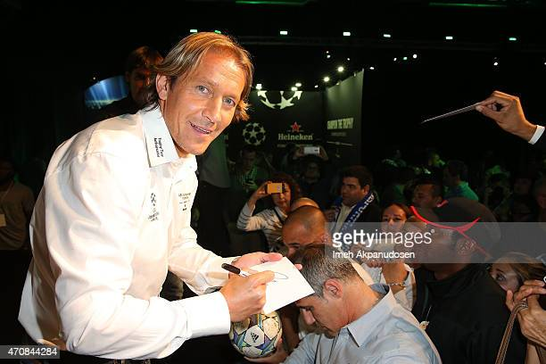 Former professional soccer player Michel Salgado signs autographs for fans during a meet and greet at The UEFA Champions League Trophy Tour presented...