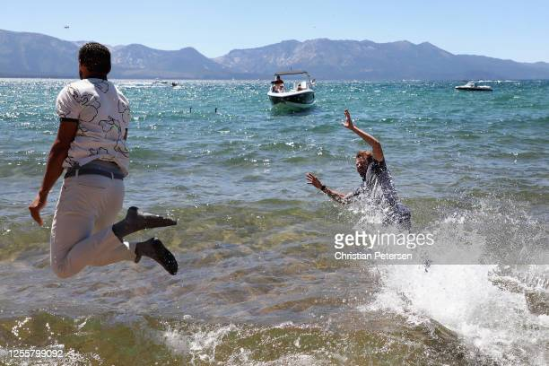 Former professional tennis athlete Mardy Fish jumps into Lake Tahoe alongside Stephen Curry after winning the American Century Championship at...