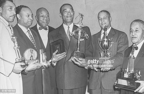 Former publisher of the Afro American Newspapers John H Murphy Jr posing smiling and holding a trophy during a golf tournament February 4 1958