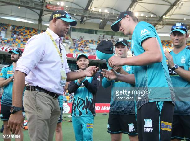 Former QLD player Andrew Symonds presents Matthew Renshaw with a Heat cap during the Big Bash League match between the Brisbane Heat and the...