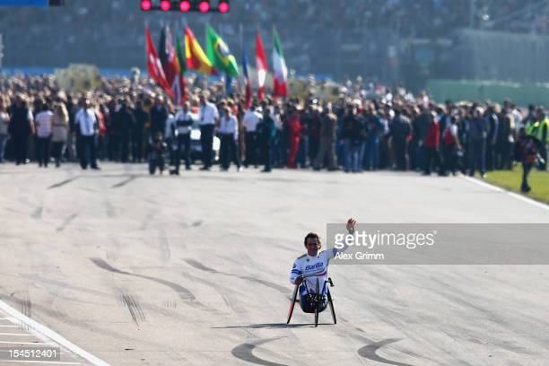 Former race driver and Paralympic Games gold medal winner Alessandro Zanardi of Italy waves to the spectators prior to the final run of the DTM 2012...