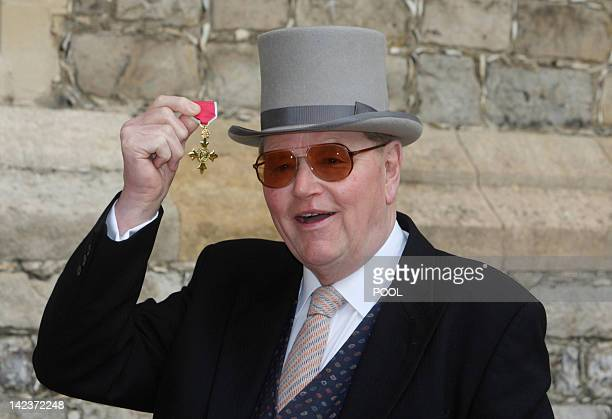 Former racehorse trainer Toby Balding poses with his medal after he was made an Officer of the Order of the British Empire by Britain's Queen...