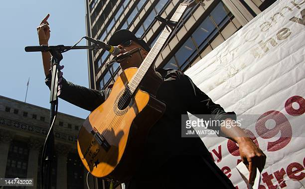 Former Rage Against the Machine guitarist Tom Morello holds up his middle finger as he performs at the National Nurses United rally in Chicago...