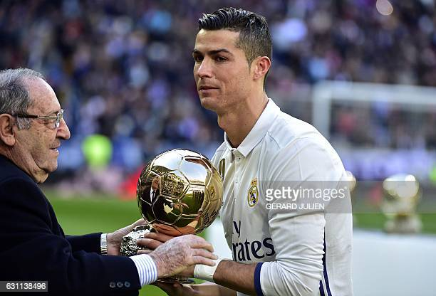 Former Real Madrid's Spanish player Francisco Paco Gento handovers the Ballon d'Or at Real Madrid's Portuguese forward Cristiano Ronaldo during the...