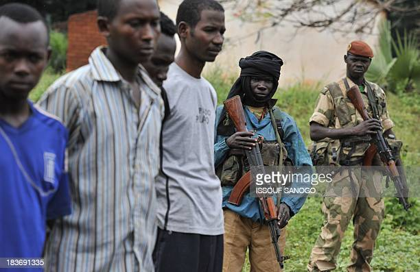 Former rebels of the Seleka coalition guard on October 8 2013 a group of men who were arrested after pretending to be Seleka rebels in Bangassou The...