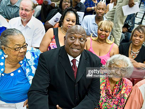 Former Redskin Rick Doc Walker squeezes between Gladine Wilson left and Arie Carpenter both are grandmothers of Alden Carpenter before giving the...