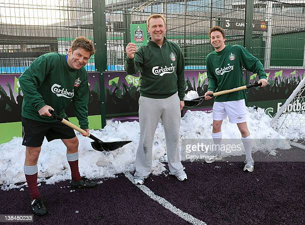Former Referee Graham Poll poses for pictures with the Carlsberg Green Card as players show commitment to the game by moving snow during a photo call...