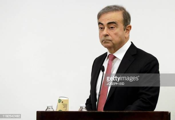 Former RenaultNissan boss Carlos Ghosn addresses a large crowd of journalists on his reasons for dodging trial in Japan where he is accused of...