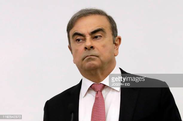 Former RenaultNissan boss Carlos Ghosn looks on before addressing a large crowd of journalists on his reasons for dodging trial in Japan where he is...