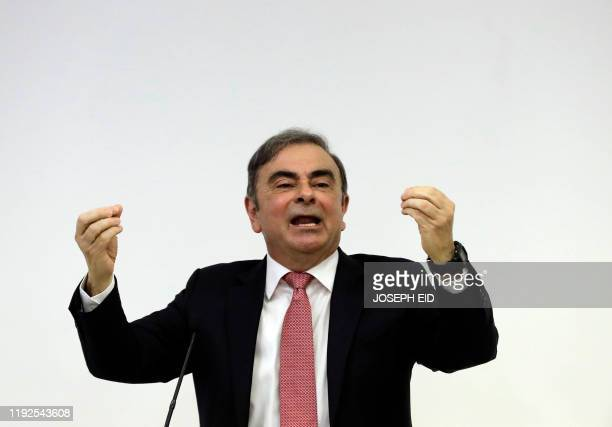 Former RenaultNissan boss Carlos Ghosn raises his hands as he addresses a large crowd of journalists on his reasons for dodging trial in Japan where...