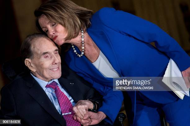 Former Republican US Senate Majority Leader Bob Dole embraces House Minority Leader Nancy Pelosi during his Congressional Gold Medal ceremony on...