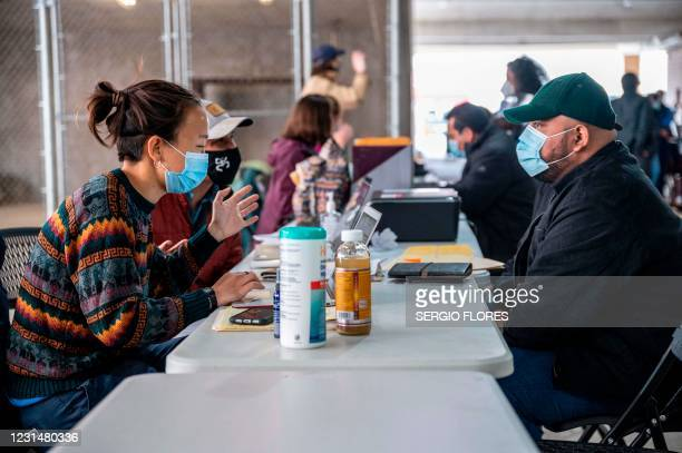 Former residents of a migrant camp in Matamoros, Mexico, receive legal and clerical help in a parking garage in Brownsville, Texas before travelling...