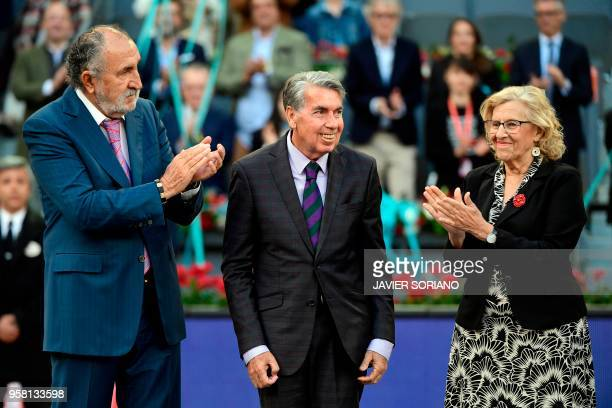 Former Romanian tennis player Ion Tiriac and mayor of Madrid Manuela Carmena applaud to former Spanish tennis player Manolo Santana during after the...