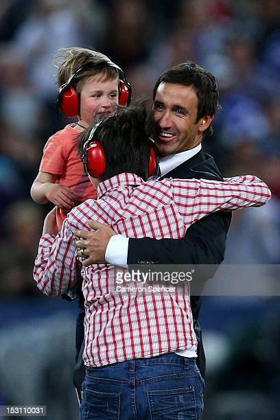 Former rugby league player Andrew Johns embraces his son's Louis Byron and Samuel at halftime during the 2012 NRL Grand Final match between the...
