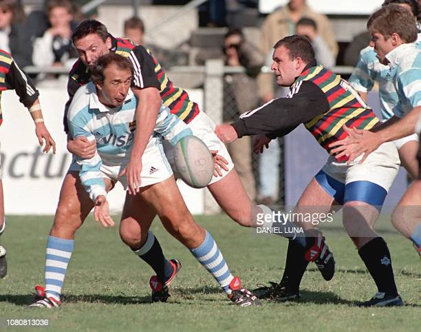 Former rugby player Hugo Porta from Argentina reaches for the ball as BerrieJon Mather tackles him 17 April 1999 in Buenos Aires during a friendly...