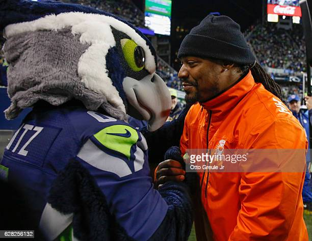 Former running back Marshawn Lynch of the Seattle Seahawks greets Blitz the Seahawks mascot during a game against the Carolina Panthers at...