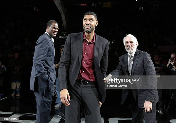 Former San Antonio Spurs star Tim Duncan reacts to the crowd as head coach Gregg Popovich and former Spur David Robinson look on while honoring the...