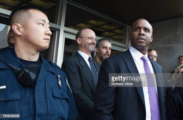 Former San Francisco Giants Major League baseball player Barry Bonds stands next a police officer and his attorney Ted Cassman after Bonds was was...