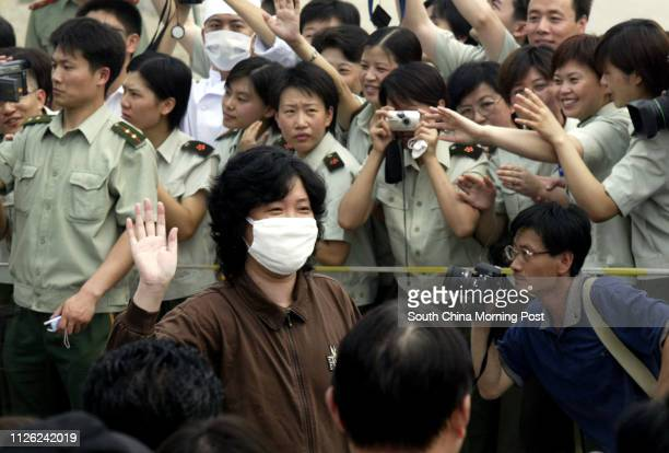 A former SARS patient waves to the crowd upon her release from the Xiaotangshan SARS hospital in the north of Beijing She was amongst a group of 18...