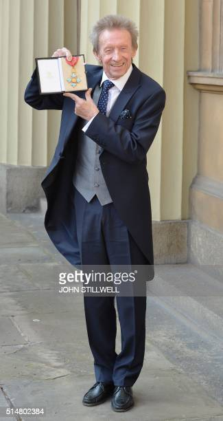 Former Scotland and Manchester United football player Denis Law holds his Commander of the Order of the British Empire medal after an investiture...
