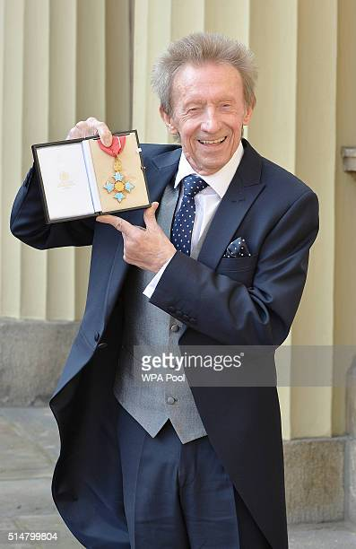 Former Scotland and Manchester United footballer Denis Law poses with his Commander of the Order of the British Empire medal that was presented to...
