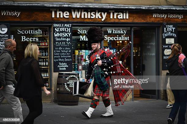 Former Scots Guards Piper David Barnet walks past a whisky shop on the Royal Mile on September 3 2015 in EdinburghScotland Plans to introduce a...