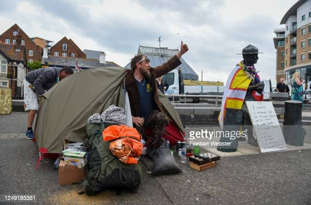 Former Scout Dan Davis celebrates at his tent, as workmen arrive to board up the Lord Baden-Powell statue on June 12, 2020 in Poole, United Kingdom....