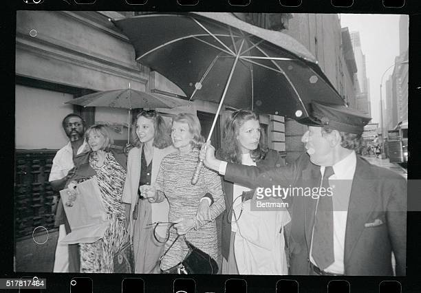 Former screen queen Rita Hayworth and her daughter Yasmin Kahn get some protection from the rain as they leave the Mark Hellinger Theatre with Kitt...