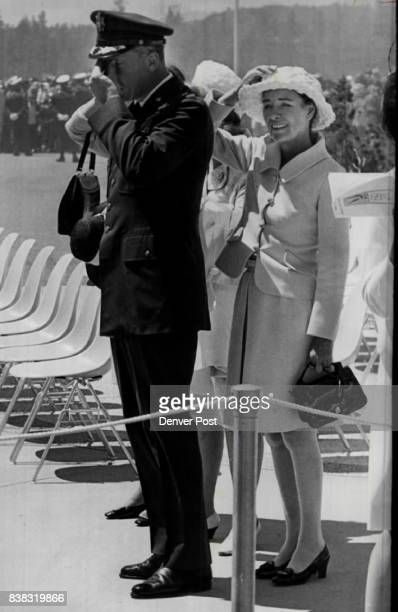 Former screen star Ella Raines holds her hat and takes cover behind her husband Brig Gen Robin Olds AFA commandant of cadets as departure of...